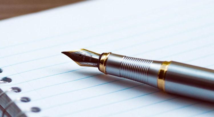 Ein Schreibblock mit einer Feder auf dem Tisch zum schreiben der Affirmationen
